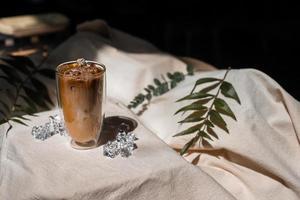 Close-up vaso de café helado con leche sobre la mesa foto