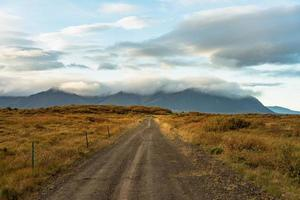 Gravel road across an autumn colored field in Iceland photo