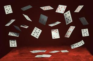 Playing cards flying and falling on a table with a red cloth photo
