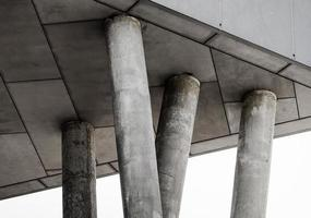 Fragment of gray concrete building with columns photo