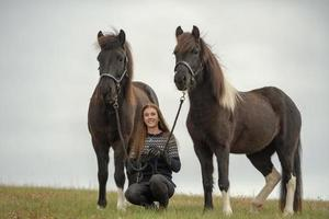 Young Swedish woman in a field with her two Icelandic horses photo