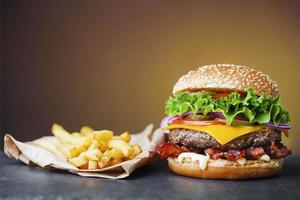 Big cheeseburger with heap of french fries on slate board photo