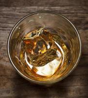 Vista superior de un solo vaso de bebida alcohólica con hielo sobre fondo de madera foto