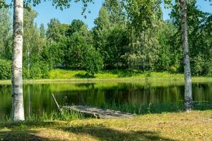 antiguo muelle de madera en un pequeño lago foto