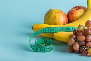 Ripe fruits and measuring tape on a blue background. The concept of diet and proper nutrition. photo