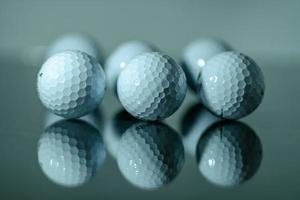 White golf balls in a row reflected on a mirror