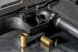 Black hand gun with two empty brass shells photo