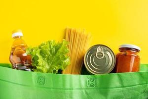 concepto de entrega de alimentos sobre un fondo amarillo. Bolsa biodegradable con productos alimenticios imprescindibles. foto