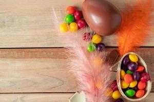 plumas de colores y dulces de pascua. huevos de chocolate para unas vacaciones sobre un fondo de madera. foto