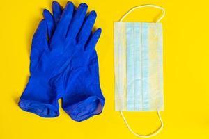 guantes de látex y mascarilla médica sobre un fondo amarillo. protección preventiva contra coronavirus. foto