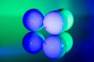 Pelotas de golf blancas iluminadas con luz verde y azul. foto