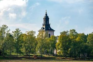 White stone church with autumn colored trees