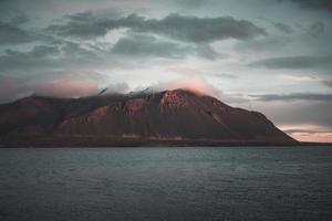 picos de montaña con nubes rosadas y agua foto
