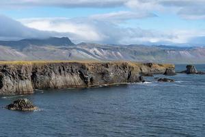 Volcanic basalt cliff on the west coastline of Iceland photo