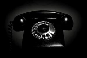Vintage landline telephone with a handset in black and white. Retro dial phone in a low key. photo