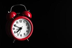 Red alarm clock on black background