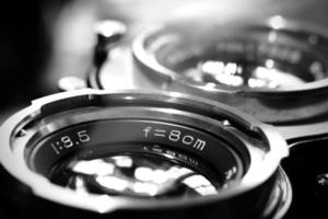 Close up image of a vintage TLR camera lenses in black and white photo