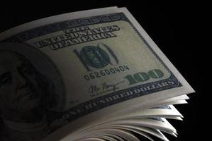 One hundred dollar banknotes on black background photo