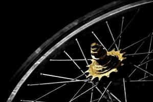 Old bicycle wheel with worn tire on black background. photo