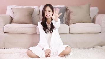 jovem mulher asiática sorrindo e acenando
