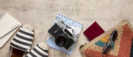 Travel flat lay with camera, shoes, and map photo
