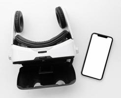 Vista superior de auriculares de realidad virtual y teléfono móvil sobre fondo blanco. foto