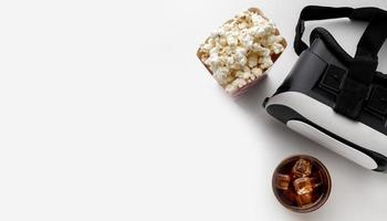 Virtual reality headset with popcorn on white background photo