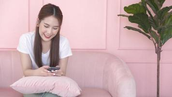 Asian Woman Sitting on Sofa Looking at Her Phone video