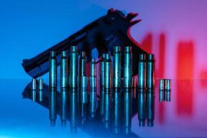Pistola con casquillos de bala en luz azul y roja. foto
