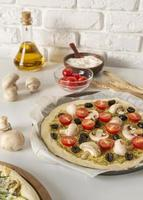 Pizza and ingredients on neutral background photo