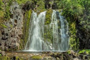 cascada que fluye por una pared de roca cubierta de musgo verde foto