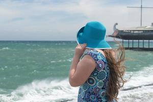 Una niña con un sombrero azul y un vestido colorido en una playa mirando al mar en Yalta, Crimea foto