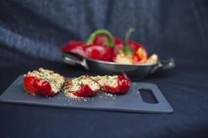 pimientos rojos rellenos en un plato y tabla de cortar foto