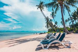 Beautiful outdoor view with sunbathing beds on the beach photo