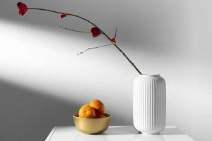 Flower vase next to a bowl of oranges photo