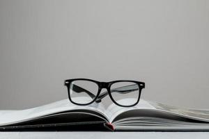 Front view open book with glasses photo