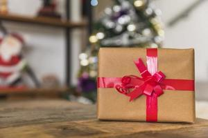 Gift box with red ribbon on table photo