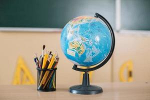 World globe and writing tools on school table photo
