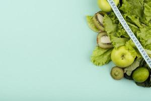 Green fruit with tape measure and copy space concept on green background photo