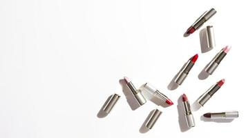 Grupo de lápices labiales metálicos sobre fondo blanco. foto