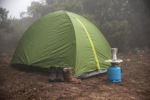 Green tent set up in foggy forest photo