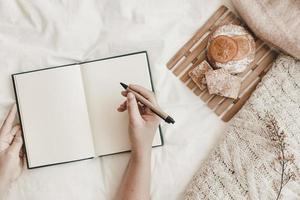Hand holding pen with opened notebook on bed photo