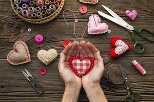 Manos sosteniendo una forma de corazón rojo sobre fondo de madera foto