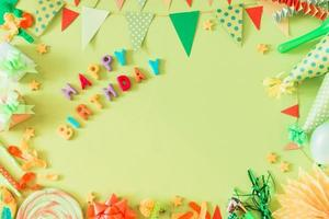 Happy birthday text with accessories on green background photo