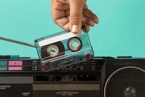 Insertar cinta en casete sobre fondo de color verde azulado foto