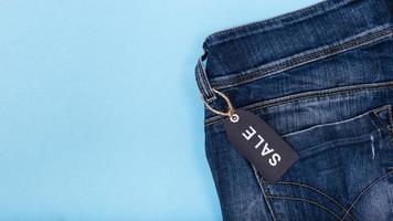Jeans con etiqueta de venta adjunta sobre fondo azul. foto