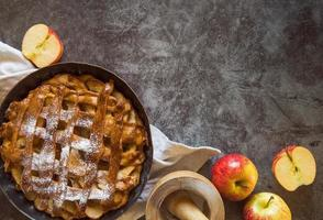 Baked apple pie on table with fruit photo
