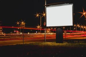 Cartelera publicitaria en blanco con semáforos borrosos en la noche foto