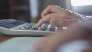 usando calculadora para calcular transações em uma caderneta bancária