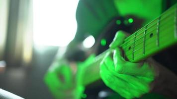 un hombre tocando la guitarra eléctrica en una habitación con luz de colores video